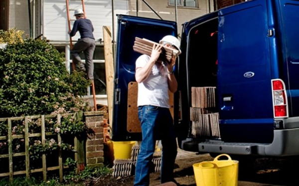 Builders unloading a van and working on a house