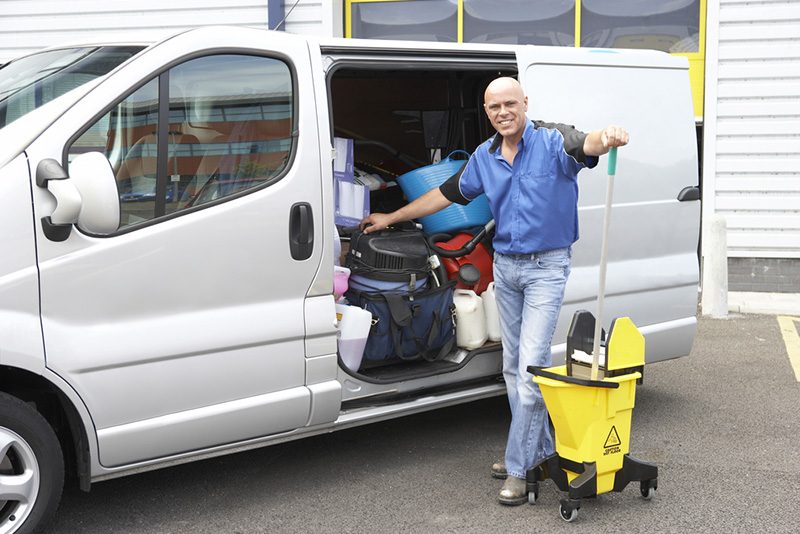 Industrial cleaner standing with a company van